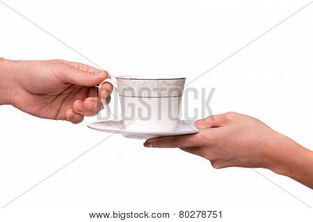 Hand giving cup and saucer