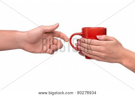 Hand passing a mug of coffee