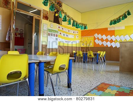 Kindergarten Classroom With Chairs And Table With Drawings Of Children