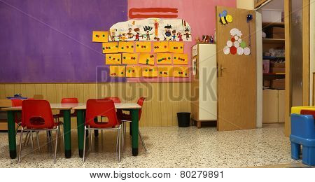 Classroom With Red Chairs And Table With Drawings Of Children