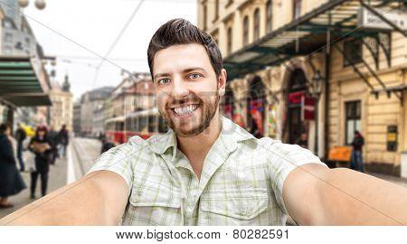 Happy young man taking a selfie photo in Prague, Czech Republic.