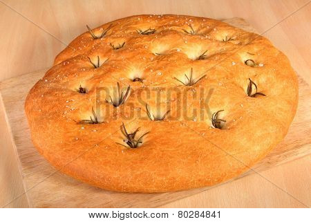 Freshly Baked Foccacia Bread With Rosemary On A Wooden Board