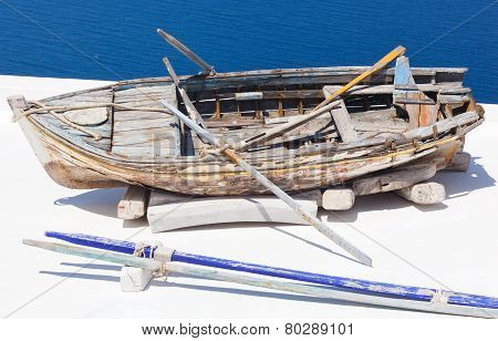 Old Damaged Rowing Boat Withpaddles And Rope