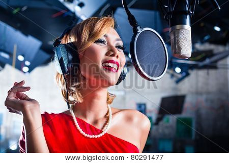 Asian professional musician recording new song or album CD in studio