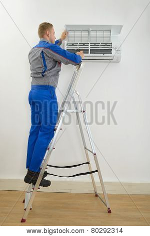 Male Technician Repairing Air Conditioner