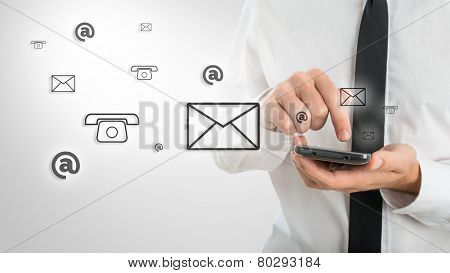 Man Using A Mobile Phone While Emitting A Clouds Of Contact Icons
