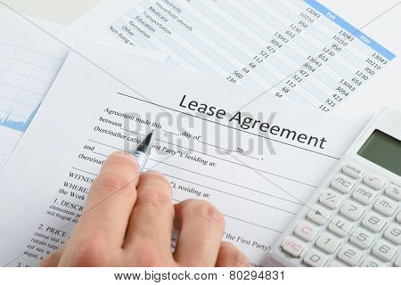 Hand With Pen And Calculator Over Agreement