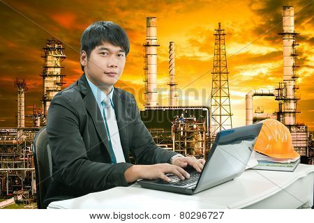 Portrait Young Engineering  Man Sittin And Working On Laptop Computer Against Oil Refinery Industry