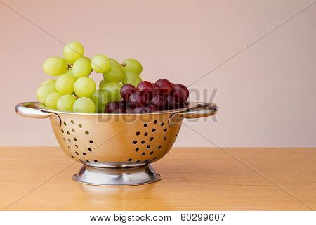 Red and green grapes in a colander