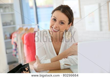 Beautiful shopgirl working in clothing store