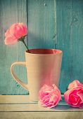 image of blue rose  - Vintage still life,mug with pink roses on blue wood background
