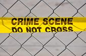 stock photo of crime scene  - Closeup of Bright yellow Crime Scene Do Not Cross tape against a chain link fence - JPG
