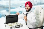 picture of indian money  - Young indian businessman with suitcase full of money - JPG