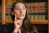 stock photo of laws-of-attraction  - Pretty lawyer thinking in the law library at the university - JPG
