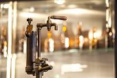 stock photo of tapping  - Vintage tap to wooden barrel full of beer - JPG
