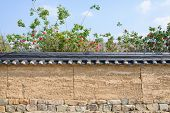 stock photo of red roof tile  - korean traditional tiled roof wall with red rose in sunny day - JPG