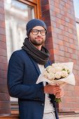 picture of toothless smile  - Handsome young man in smart casual wear holding bouquet of flowers and smiling while standing at the street - JPG