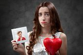 foto of upset  - Upset woman holding photo card with boyfriend and broken heart - JPG