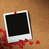 foto of polaroid  - polaroid style photo frames on corkboard with paper heart - JPG