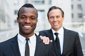 image of shoulders  - Confident senior man in formalwear holding hand on shoulder of young African man that looking at camera and smiling - JPG