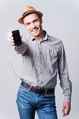 stock photo of fedora  - Handsome young man in fedora showing his MP3 player and smiling while standing against grey background - JPG