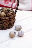 picture of wooden basket  - Quail eggs in a wicker basket on a wooden background with kitchen towel - JPG