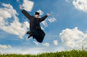 picture of graduation hat  - Young smiley graduate student in gown jumping over blue sky - JPG