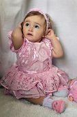 stock photo of headband  - little girl in a pink dress straightens headband - JPG