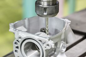 stock photo of tapping  - Tapping aluminum automotive part by cnc machining center - JPG