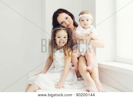 Portrait Of Mother With Two Daughters In White Room Near Window