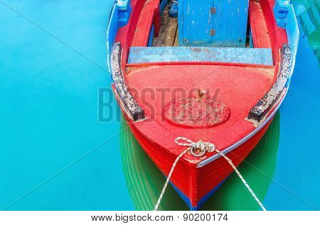 Empty Red Wooden Boat With Blue Broadside Moored In Port With Silent Azure Water