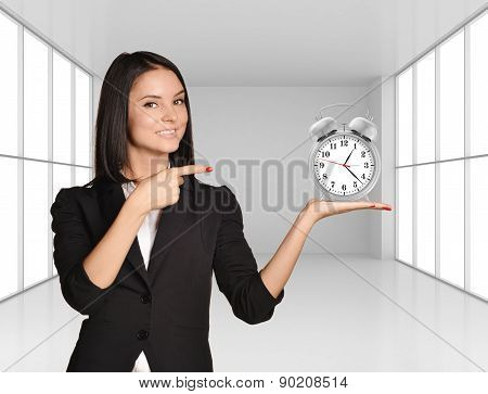 Young girl holding silver alarm clock on hand