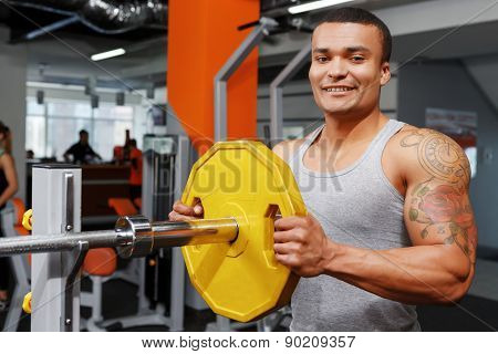Young man preparing his barbell.