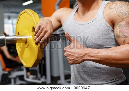 Weightlifter leaning on barbell in gym