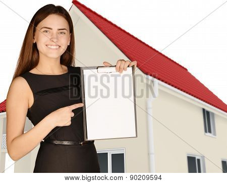 Office girl on background of house holding clip board pointing forefinger