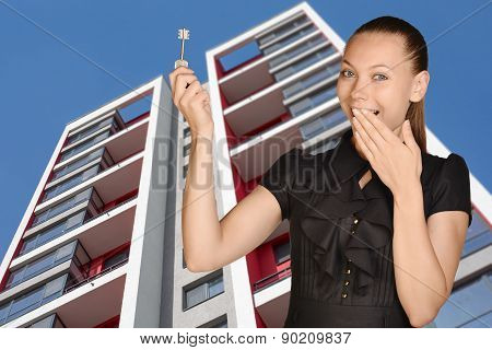 Joyful girl standing on background of building and is holding keys