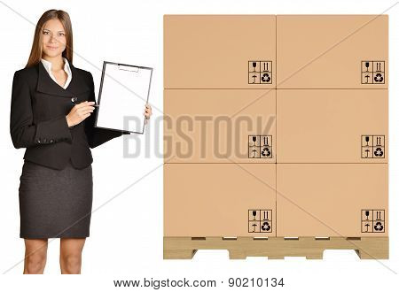 Office Girl standing with cardboard boxes on pallet and showing in clipboard
