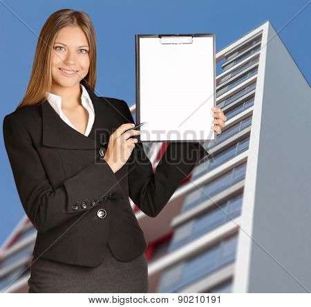 Business woman standing on background building, and indicates ballpoint pen in the clipboard