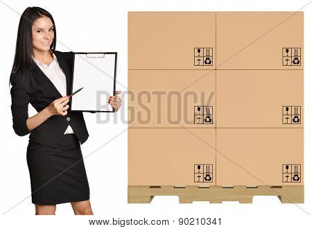 Girl standing with cardboard boxes on pallet and showing in clipboard