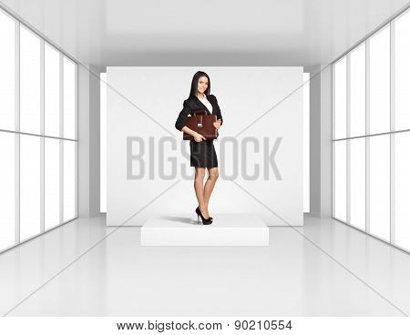 Young Girl stands on a podium in an empty room light