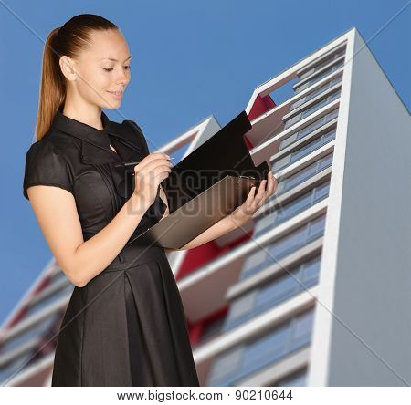 Office girl standing on background of building and writes pen in clipboard