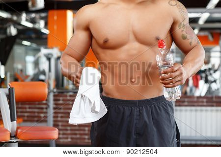 Man holding bottle of water in gym