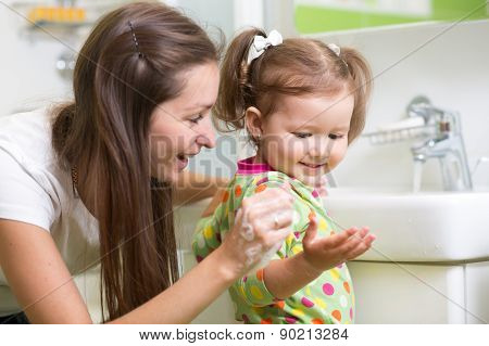 Smiling girl child and her mom washing hands and face with soap in the bathroom. Hygiene.