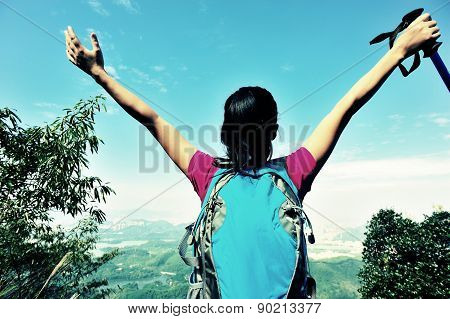 young cheering woman hiker open arms at mountain peak
