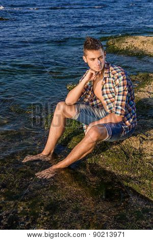 Attractive Young Fashion Sexy Man Sitting On A Rock Near The Sea Water