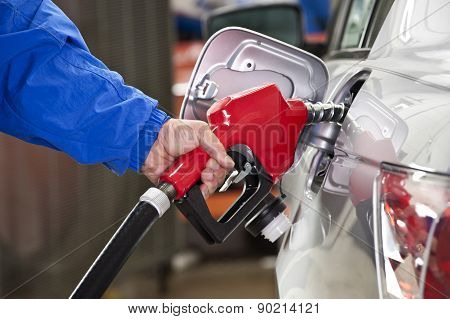 Man Pumping Gas With Blue Jacket