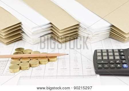 Pencil On Pile Of Gold Coins With Calculator