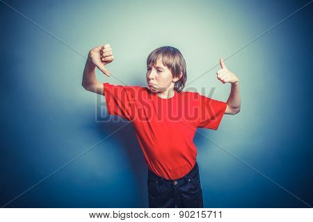 European-looking boy of ten years thumbs up, thumbs down on a gr