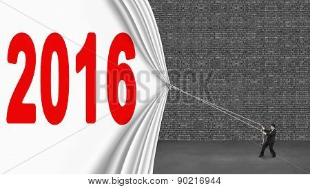 Businessman Pulling Down 2016 Curtain Covering Old Dark Brick Wall