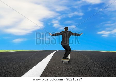 Businessman Skateboarding On Asphalt Road With Blue Sky